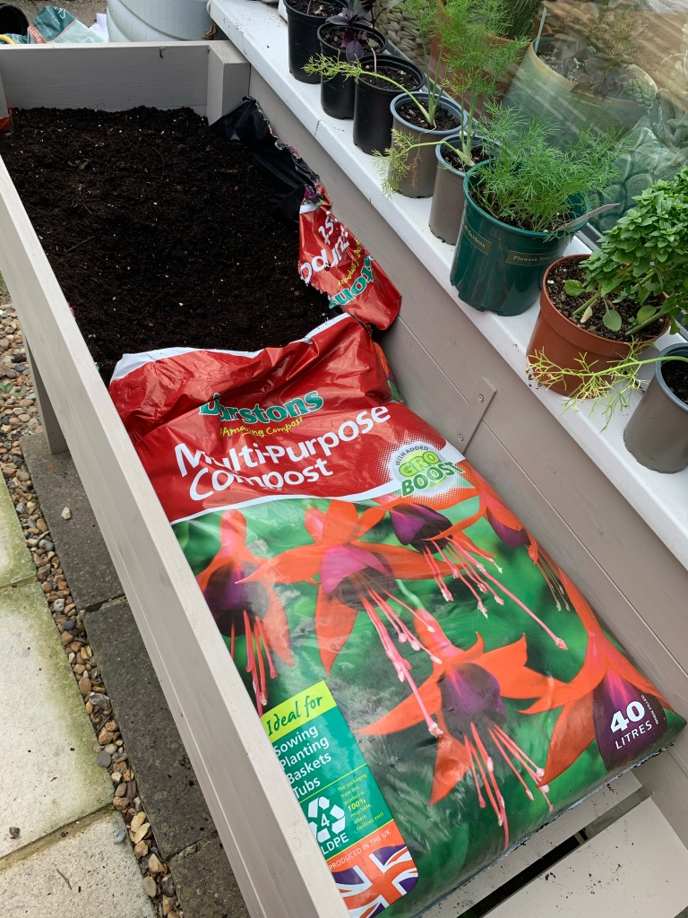 Lining herb planter with compost bags